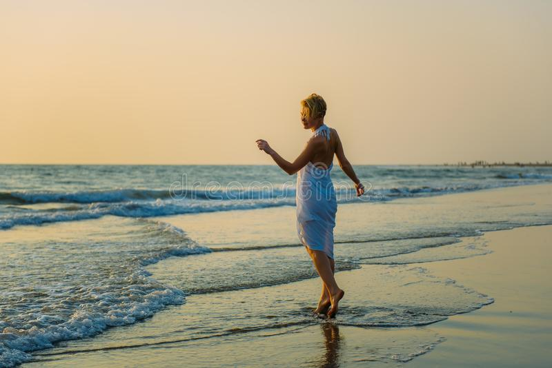 Charming slender blonde in stylish dress stands in waves on the sea. Young woman walks barefoot along the surf and enjoys the rest stock images