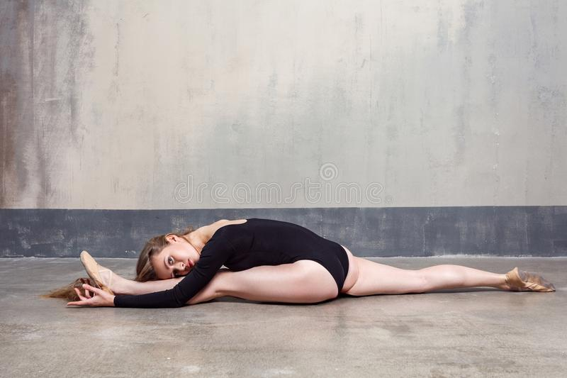 Charming slender young adult woman doing the splits royalty free stock image