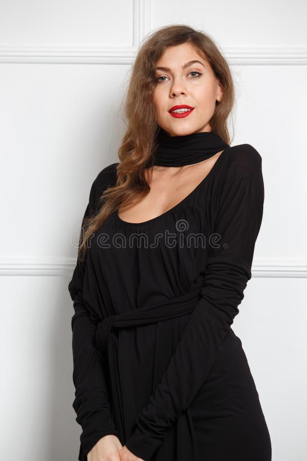 Charming slim girl dressed in a stylish black long dress poses against a white wall in the room stock photography