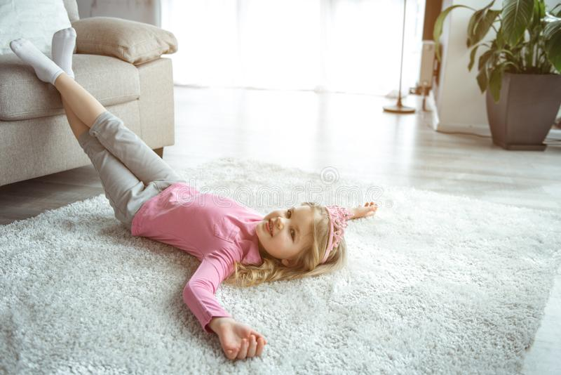 Cheerful little princess relaxing on flooring at home stock photo