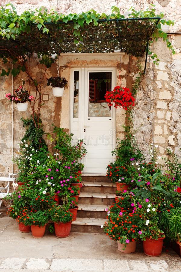 Charming small home with white front door and summer garden containers filled with annual flowers. House architecture facade window exterior building royalty free stock images