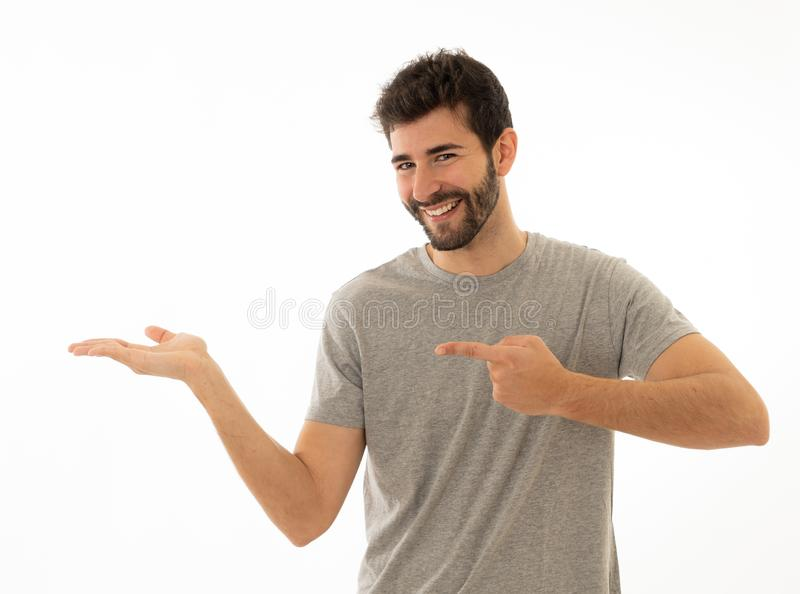Charming smiling young man pointing finger at empty copy space for advertisement royalty free stock image