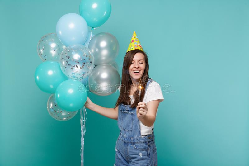 Charming smiling young woman in birthday hat holding burning sparkler and celebrating with colorful air balloons. Isolated on blue turquoise background stock photos