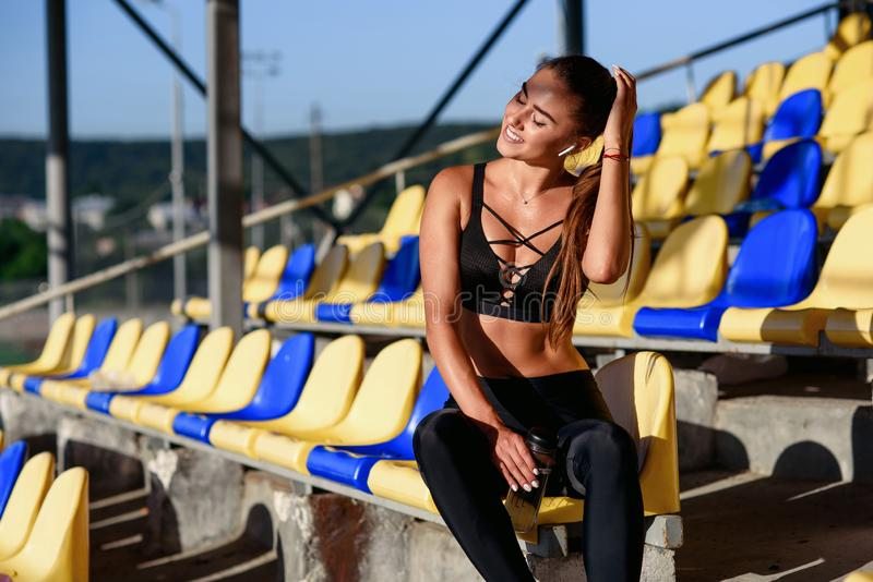 A charming sports girl with a bottle of water sits at the stadium tribune at a break between heavy trainings and listens. To music. Healthy active lifestyle stock photo