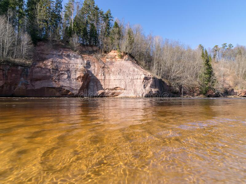 Charming spring landscape with sandstone cliffs on the river bank, fast flowing and clear river water. Kuku cliffs, Gauja river, Latvia stock photography
