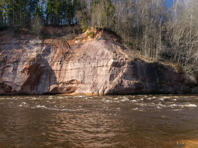 Charming spring landscape with sandstone cliffs on the river bank, fast flowing and clear river water. Kuku cliffs, Gauja river, Latvia royalty free stock photography