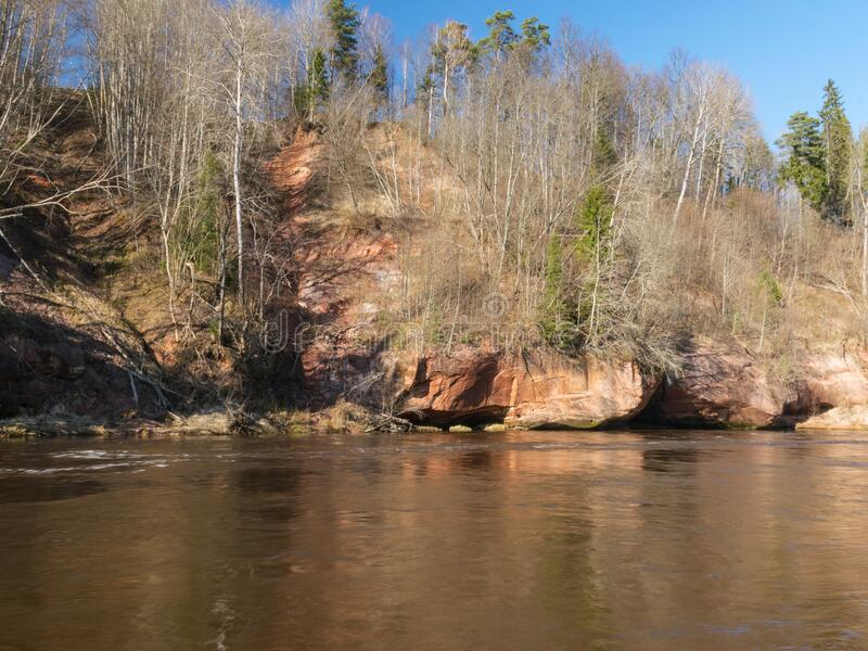 Charming spring landscape with sandstone cliffs on the river bank, fast flowing and clear river water. Kuku cliffs, Gauja river, Latvia royalty free stock photos