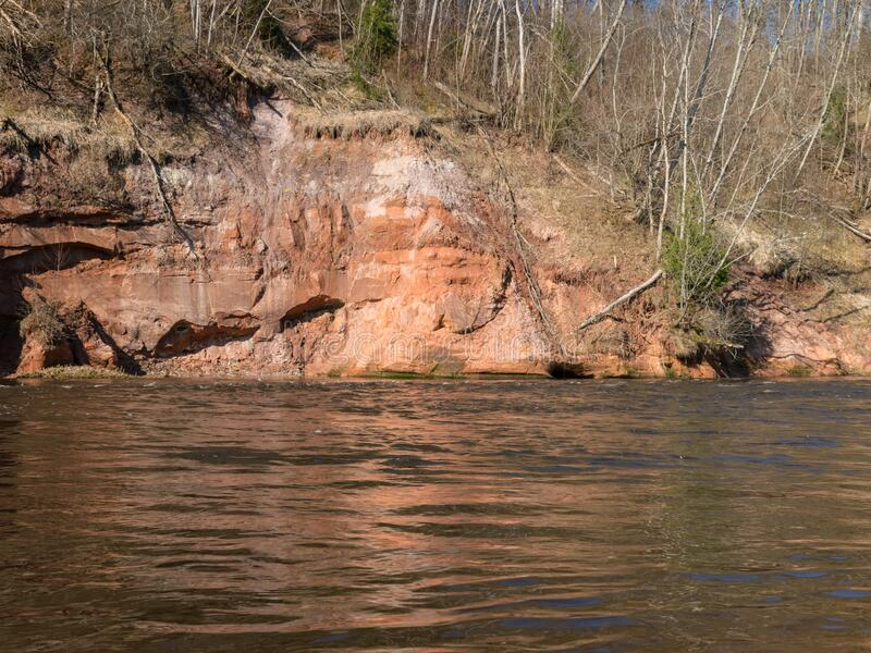 Charming spring landscape with sandstone cliffs on the river bank, fast flowing and clear river water. Kuku cliffs, Gauja river, Latvia royalty free stock photo