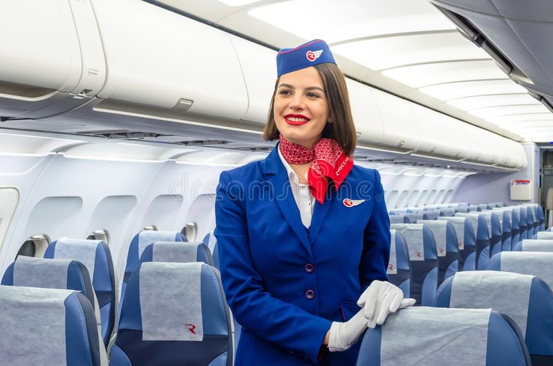 Charming Stewardess Dressed In Uniform in the passenger cabin of the aircraft. Russia, Saint-Petersburg. 23 November, 2017. royalty free stock photos