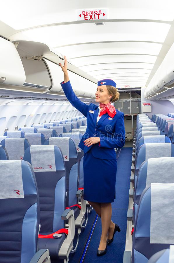 Charming Stewardess Dressed In Uniform in the passenger cabin of the aircraft. Russia, Saint-Petersburg. 23 November, 2017. royalty free stock photo