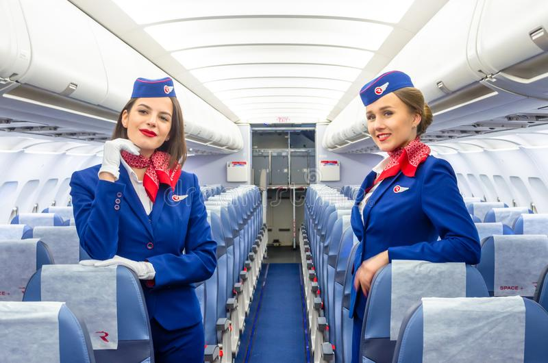Charming Stewardess Dressed In Uniform in the passenger cabin of the aircraft. Russia, Saint-Petersburg. 23 November, 2017. stock photography