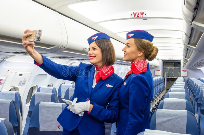 Charming Stewardess Dressed In Uniform in the passenger cabin of the aircraft. Russia, Saint-Petersburg. 23 November, 2017. stock photo