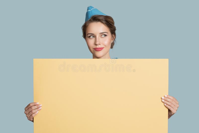 stewardess holding empty yellow paper banner in hands royalty free stock photography