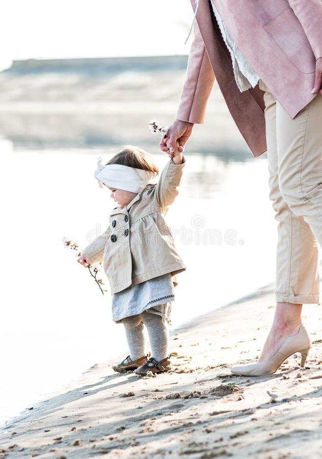 Baby girl holding mom`s hand on the sandy shore near the river. Charming stylish baby girl holding mom`s hand on the sandy shore near the river royalty free stock photos