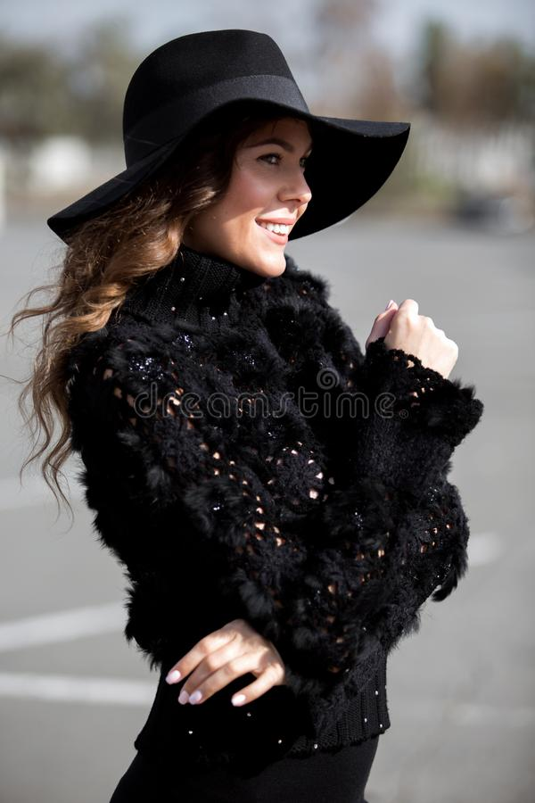 Charming stylish brunette girl dressed in a stylish knitted black sweater with fur, black skirt and fashionable hat with stock photography