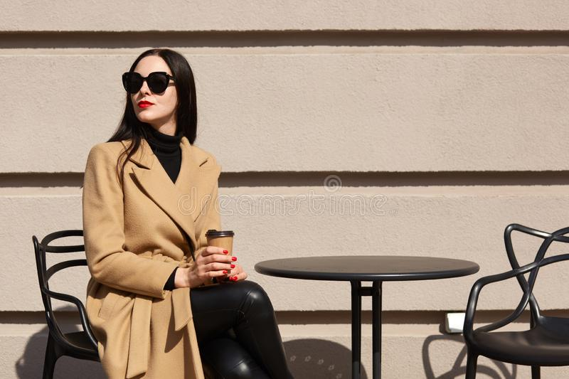 Charming stylish model with red lipstick wearing big trendy sunglasses, beige coat, black sweater and trousers, holding papercup. Of strong coffee, sitting royalty free stock photography