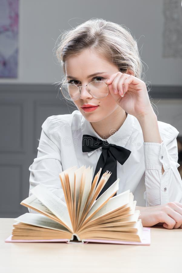Charming successful businesswoman in glasses with a book at the stock photography