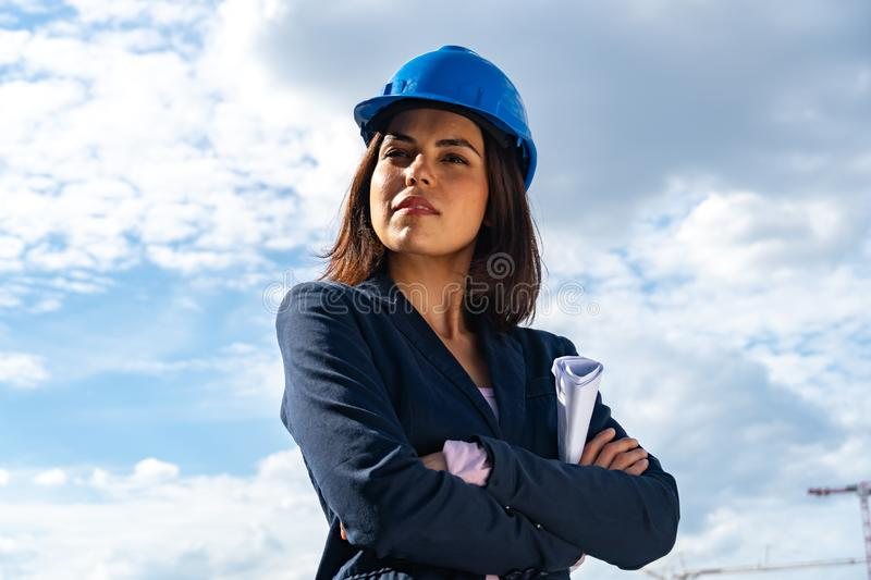 Charming and successful woman architect posing with folded arms. Low-angle shot. Low angle portrait of a beautiful and successful lady architect wearing a blue royalty free stock images
