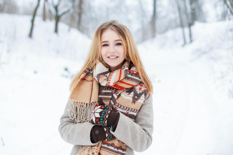 Charming sweet young girl in a winter stylish coat in a vintage wool scarf in stylish warm mittens royalty free stock photo