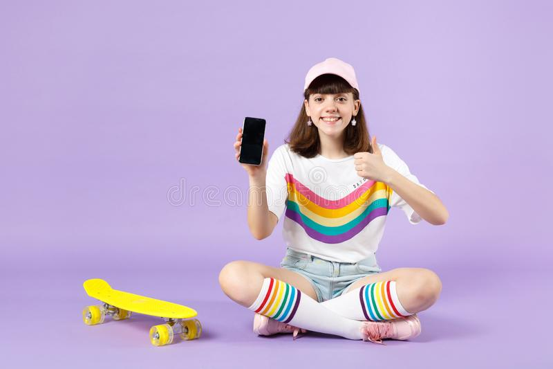 Charming teen girl sitting near skateboard holding mobile phone with blank empty screen, showing thumb up isolated on royalty free stock image