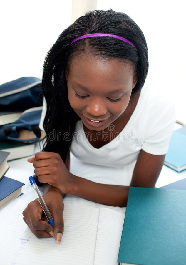 Charming teen girl studying lying on her bed royalty free stock photography