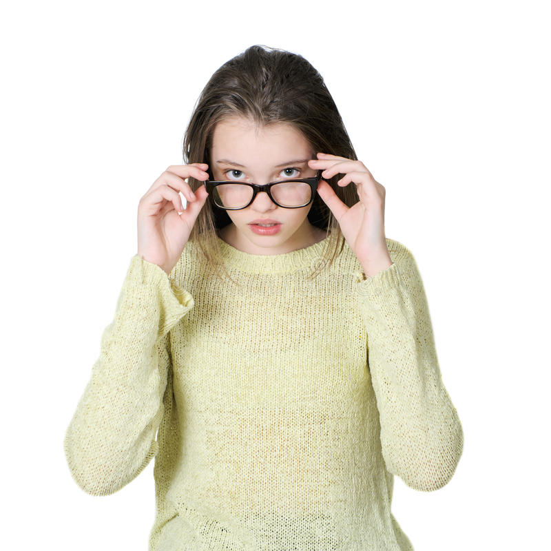 Charming teenage girl dresses glasses for vision. royalty free stock photo