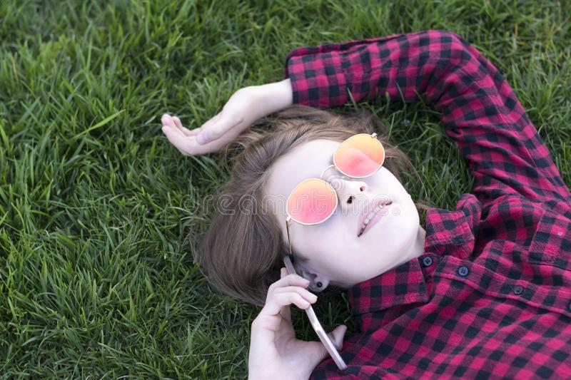 Pretty model spending time in park with phone royalty free stock photography