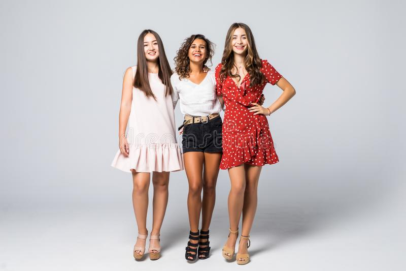 Charming three beautiful multiethnic young adult friends with dresses smiling and looking at camera isolated on white wall. Studio stock image