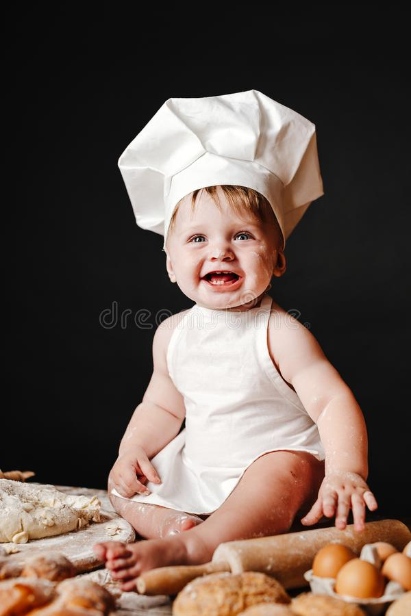 Adorable infant on table with dough. Charming toddler baby in hat of cook and apron sitting on table with bread loaves and cooking ingredients laughing happily royalty free stock photos