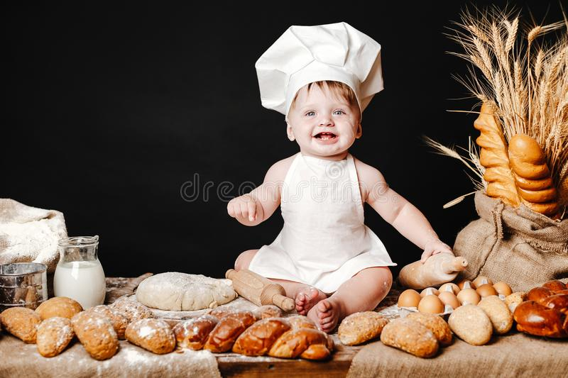 Adorable infant on table with dough. Charming toddler baby in hat of cook and apron sitting on table with bread loaves and cooking ingredients laughing happily royalty free stock photography