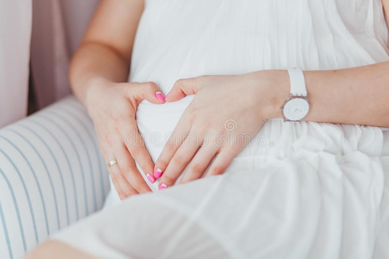 Charming tummy which the pregnant woman in a white dress embraces. The pregnant girl with pink manicure embracing belly stock photography