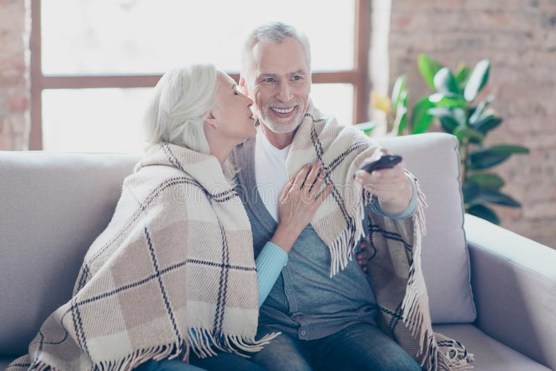 Charming two elderly people are sitting on a couch at home resting relaxing at the weekend talking and watching tv. The man is ch stock photography