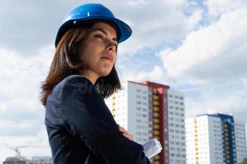 Charming woman architect posing with folded arms. Portrait of a beautiful and successful lady architect wearing a blue safety helmet and posing outdoors with royalty free stock photo