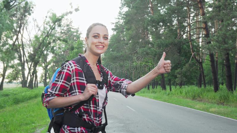 Charming woman with backpack hitchiking on countryside road. Charming woman with backpack hitchhiking on countryside road. Beautiful female traveler catching a stock photos