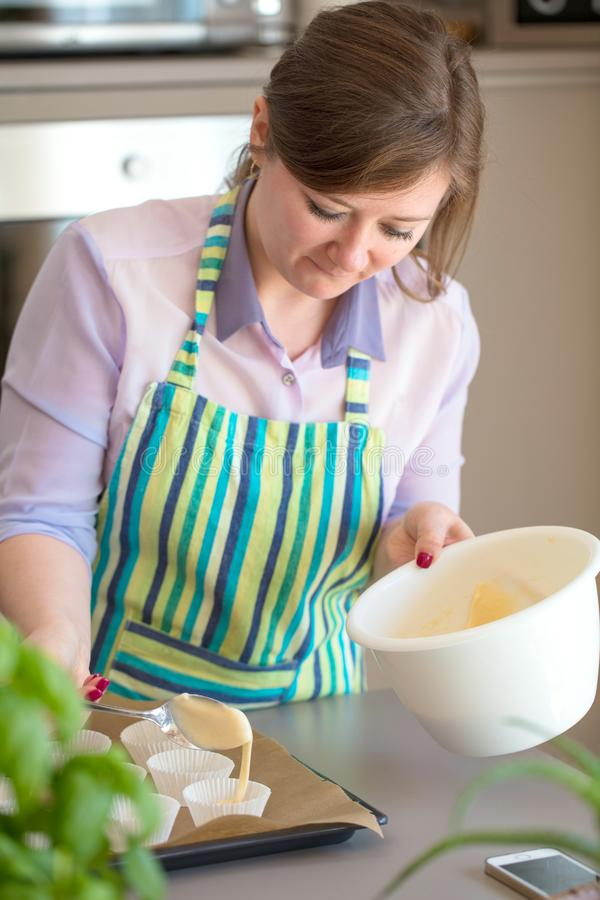 Charming woman baking in the kitchen at home blueberry muffins royalty free stock photography