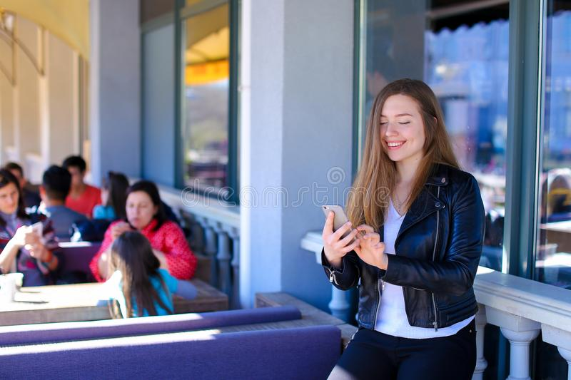 Charming woman chatting by smartphone at street cafe. stock image