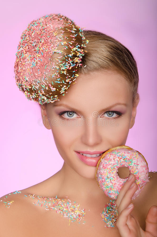 Charming woman with creative hairstyle from donut. On pink background stock photography