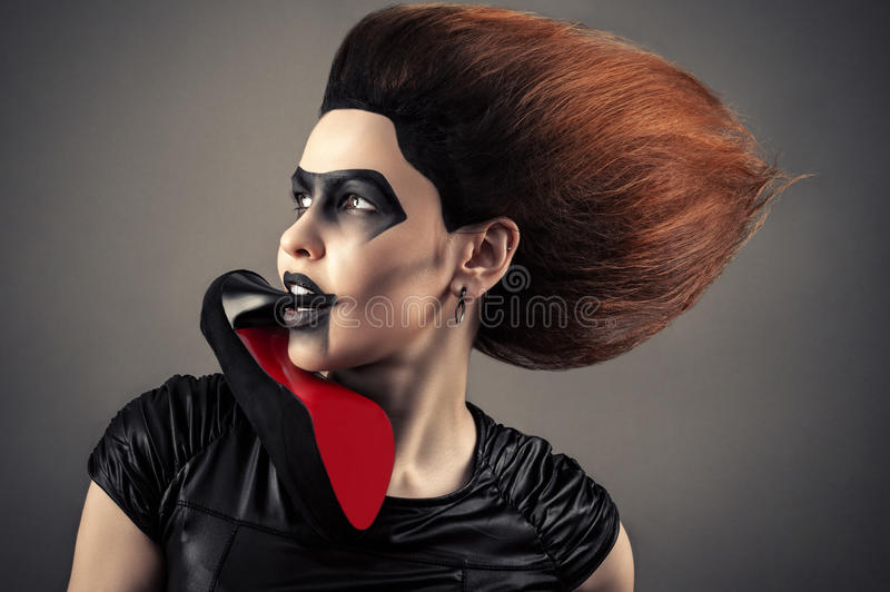 Charming woman with a dark makeup and lush hairstyle with heel in mouth royalty free stock photography