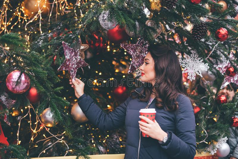 Charming woman with hairstyle, makeup and coffee looks at Christmas trees decorations stock image