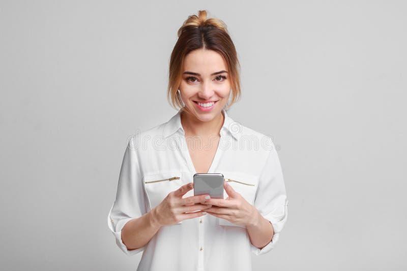 Charming woman holding smartphone, grey studio background stock image
