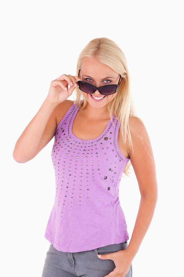 Charming woman peeking over her sunglasses stock photo