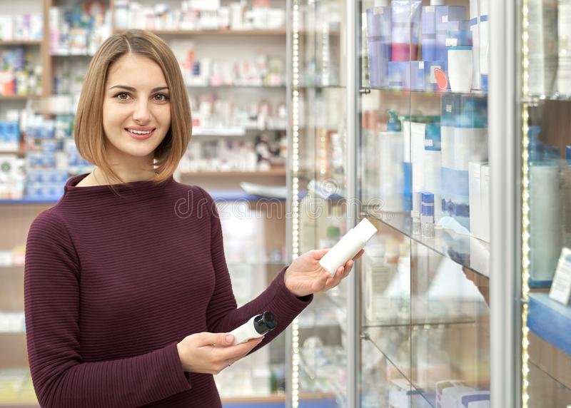 Beautiful woman holding cosmetic bottles in pharmacy. royalty free stock photography