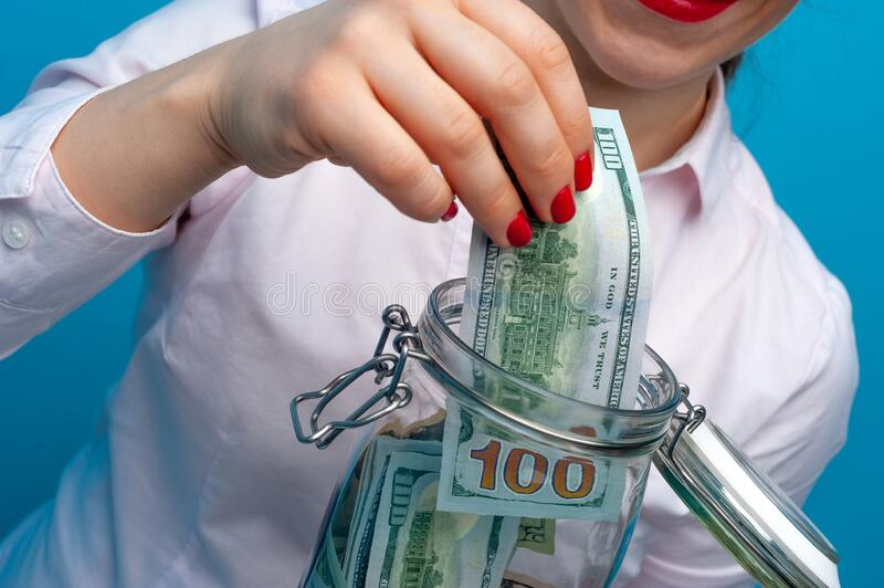 Charming woman puts a banknote in bank with paper royalty free stock image