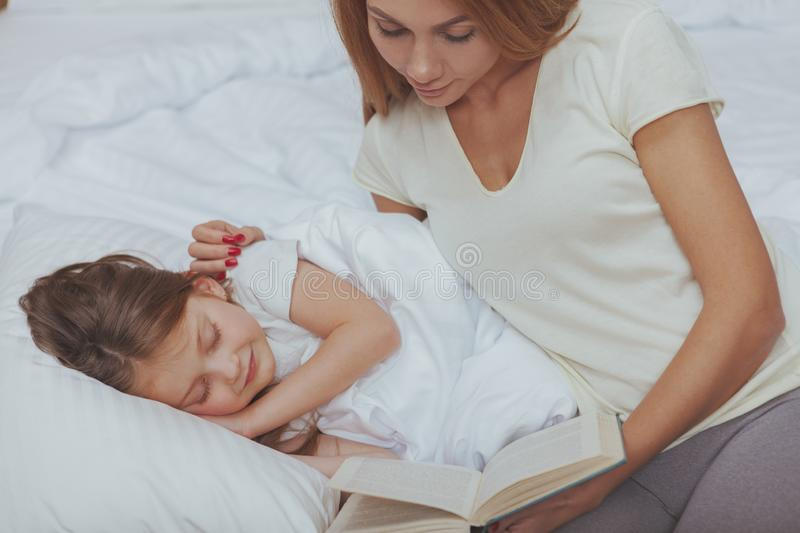 Charming woman reading a book to her little daughter royalty free stock image
