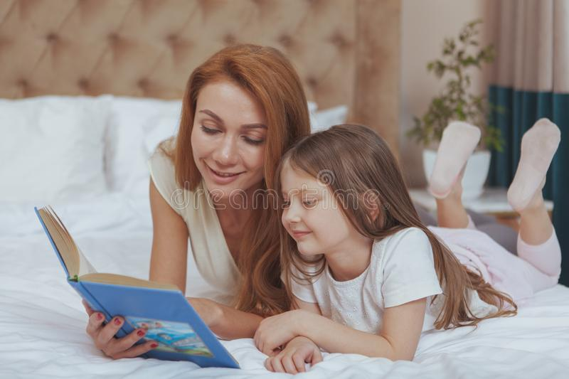 Charming woman reading a book to her little daughter stock photos