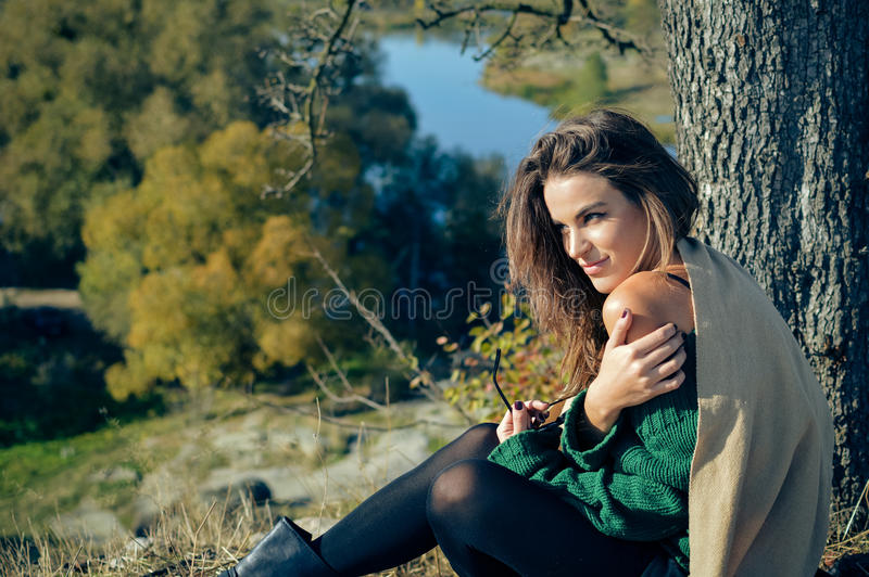 Charming woman in shawl sunning under tree on. Picture of charming elegant young woman in shawl dreaming on riverside. Pretty girl sunning under big tree on royalty free stock photos