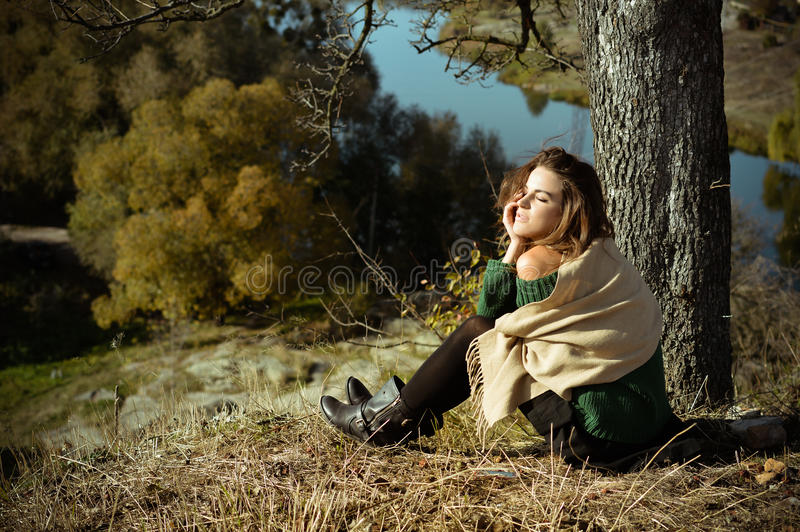 Charming woman in shawl sunning under tree on. Picture of romantic beautiful young lady in shawl dreaming on riverside. Pretty girl sunning under big tree on stock image