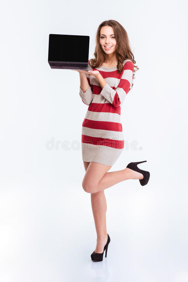 Charming woman showing blank laptop computer screen. Full length portrait of a happy charming woman showing blank laptop computer screen isolated on a white stock photo