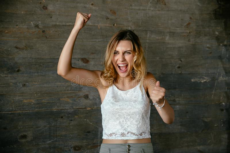 Charming woman showing winning sign. Happy successful woman showing winning gesture, raises fists as shows her big fortune. Dressed up in white singlet royalty free stock image