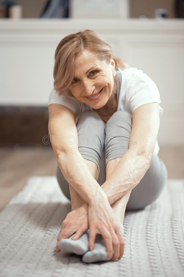 Smiling woman is having a rest sitting after practicing yoga royalty free stock images